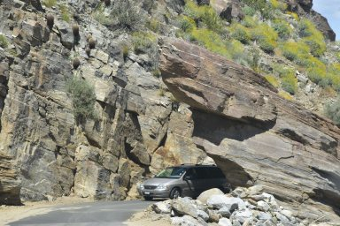The road that the van is on ly wide enough for a car and a half. The rocks appear fake.